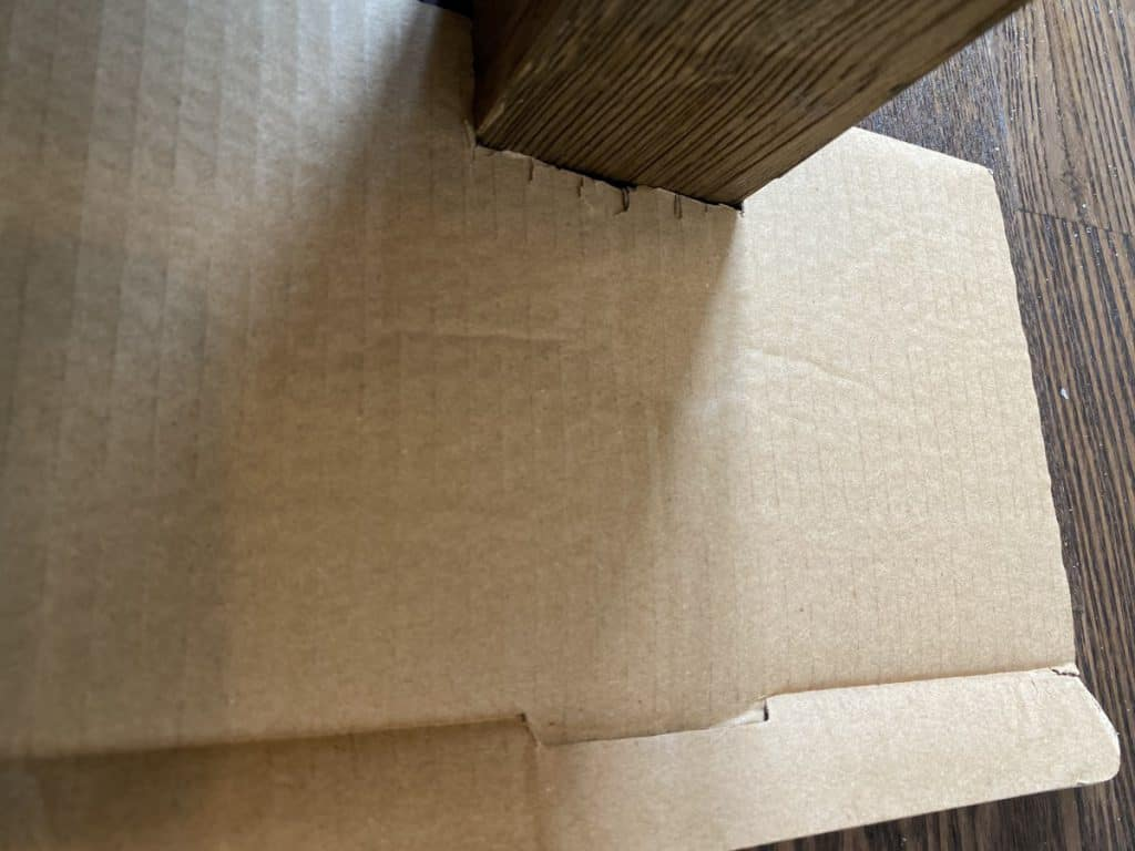 using cardboard to mark out the shape to cut carpet tiles for your garage